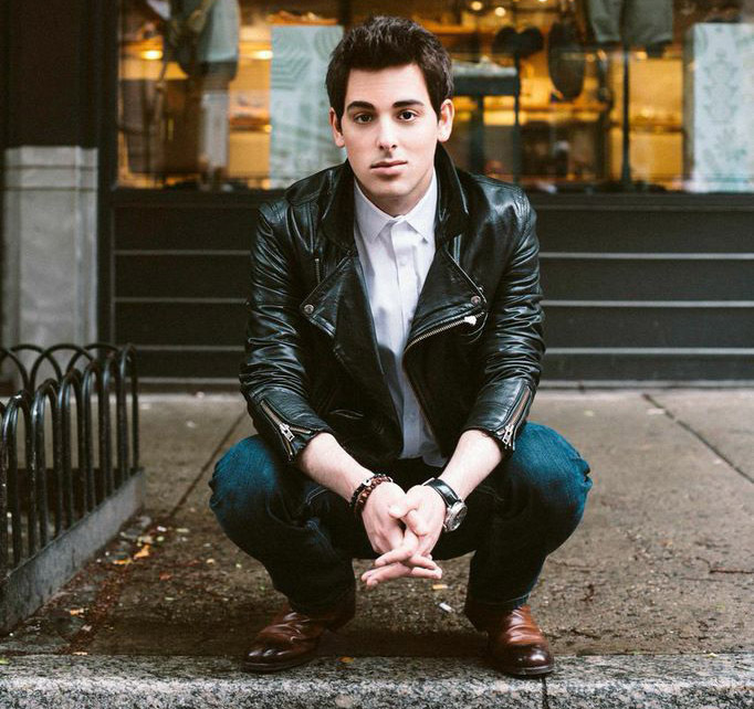 Jackson Harris crouching in a leather jacket and jeans. Photo credit: Mike Lerner