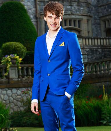 Ben from Disney's Descendants is posing in front of Auradon Prep in a blue suit