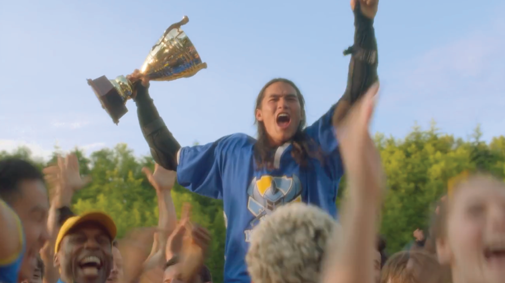 BooBoo Stewart as his character Jay from Disney's Descendants in his jousting uniform holding a trophy in a screenshot