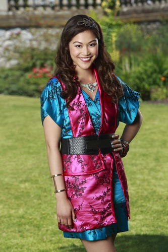 Lonnie from Disney's Descendants is posing in front of Auradon Prep in a blue and pink kimono style dress
