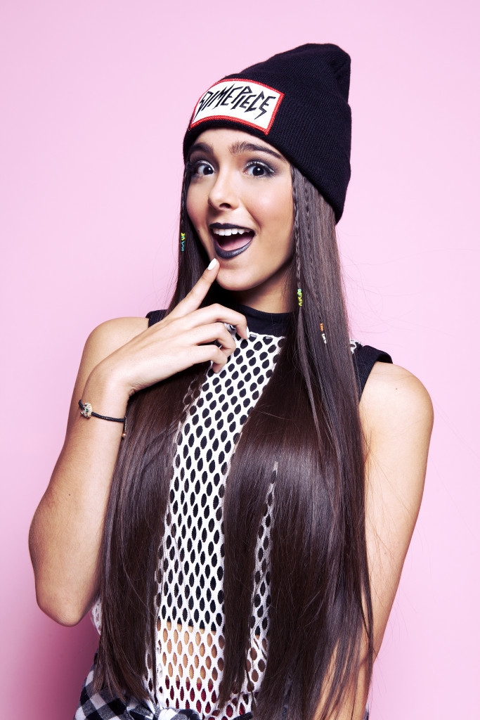 Sammi Sanchez is posing in front of a light pink background wearing a beanie and a white top posing with her mouth open in a shocked look.