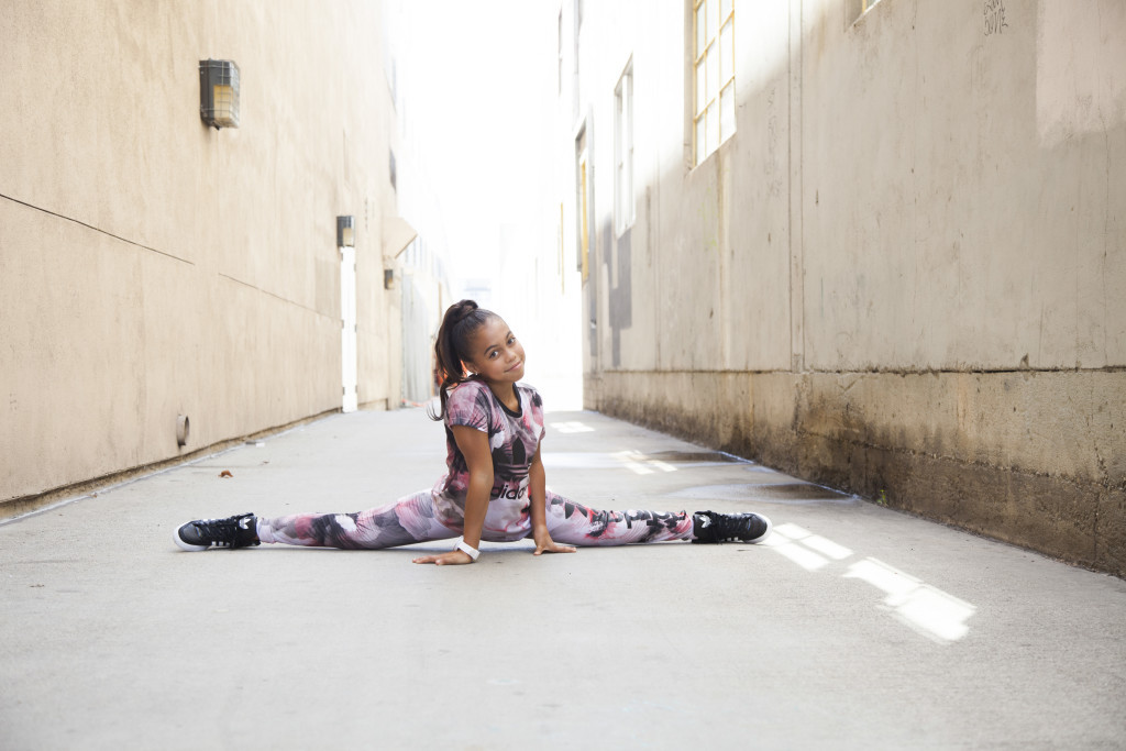 Asia Monet Ray doing the splits in an alleyway.