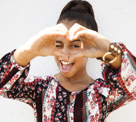 Asia Monet Ray is holding up her hands in the shape of a heart in front of her face.