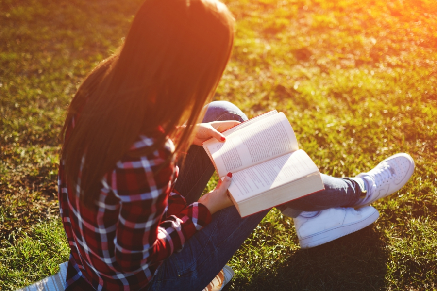 Girl wearing a flannel, jeans and white sneakers sitting in the grass reading