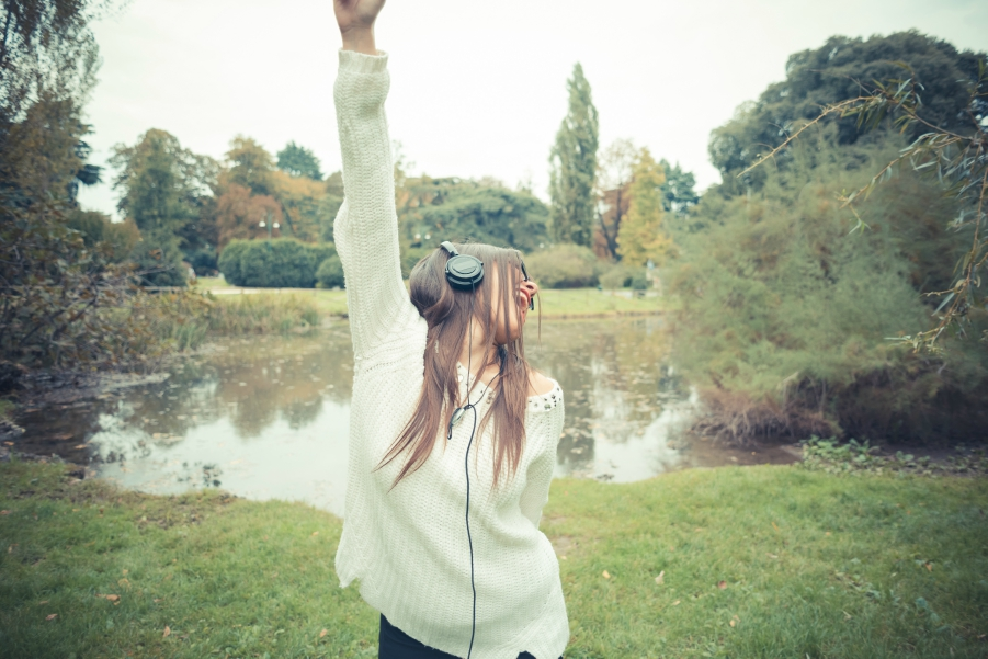 Girl standing in front of a lake pumping her fist into the air while she is listening to music through headphones