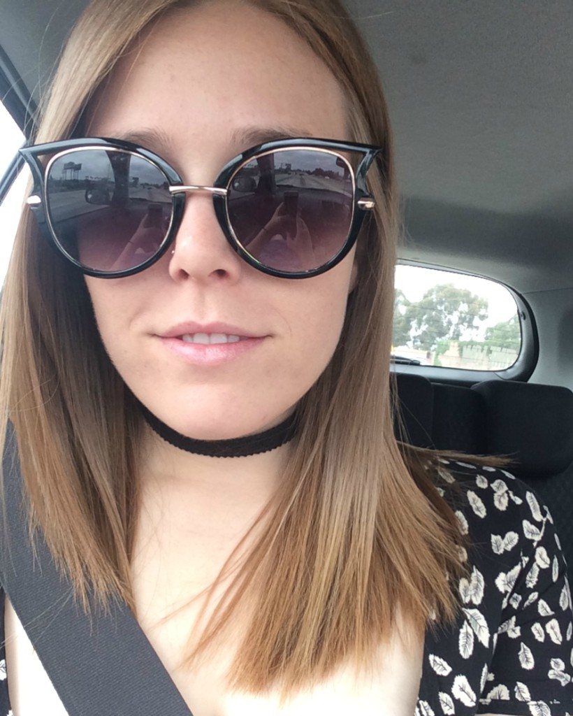 Girl wearing sunglasses taking a selfie in a car