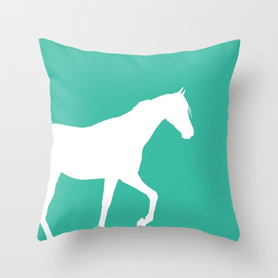 Outline of a horse on a teal pillow