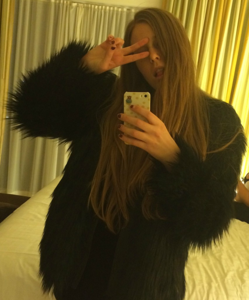 Girl wearing a black faux fur jacket while holding up a peace sign while taking a mirro selfie