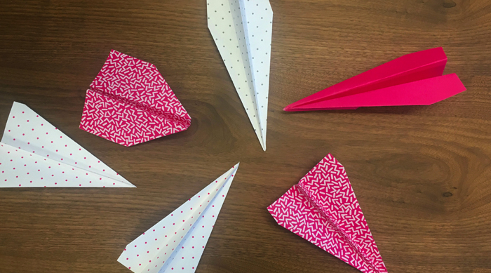 Pink and white paper airplanes