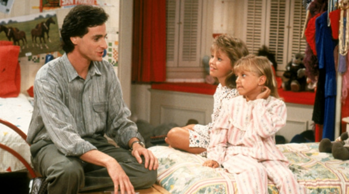 Danny Tanner sitting on a bed with DJ Tanner and Stephanie Tanner in a scene from Full House