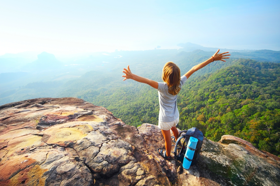 Girl on top of a mountain with her hands up