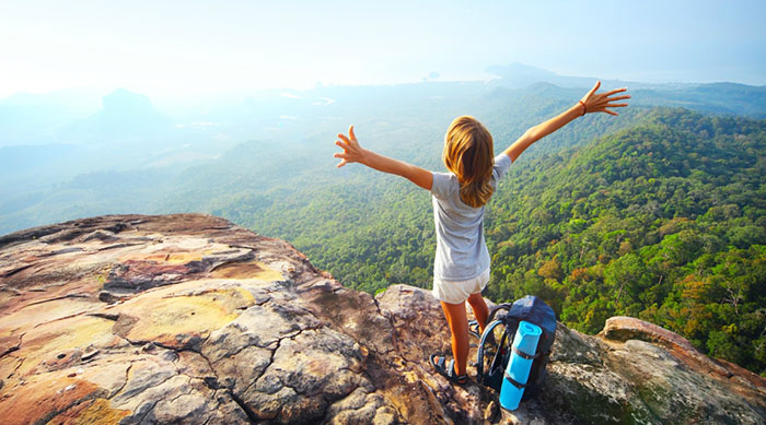 Girl with her arms stretched out on top of a mountain