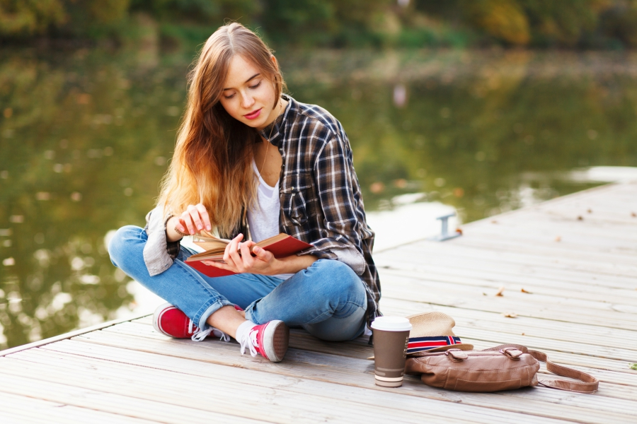 A teen girl reading a book by the lake