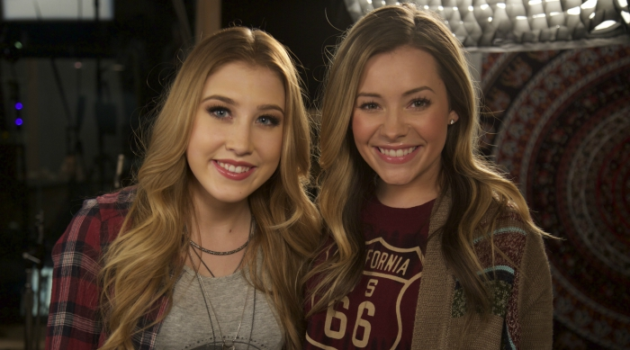 Country duo Maddie & Tae smiling at the camera