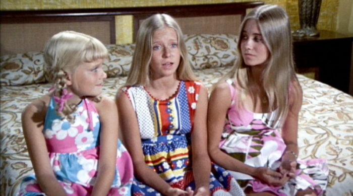 Cindy, Jan and Marcia from The Brady Bunch sitting together on a bed