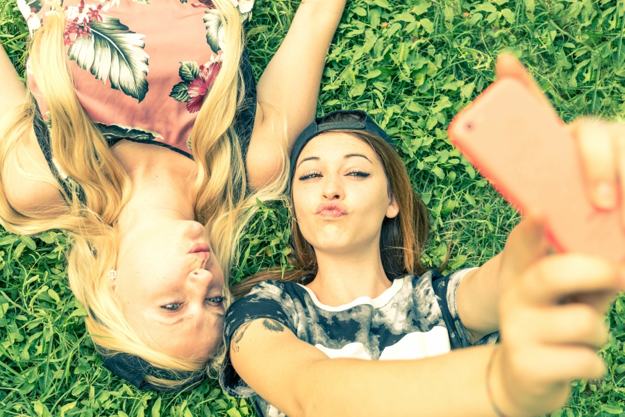 Two girls laying in the grass taking a selfie