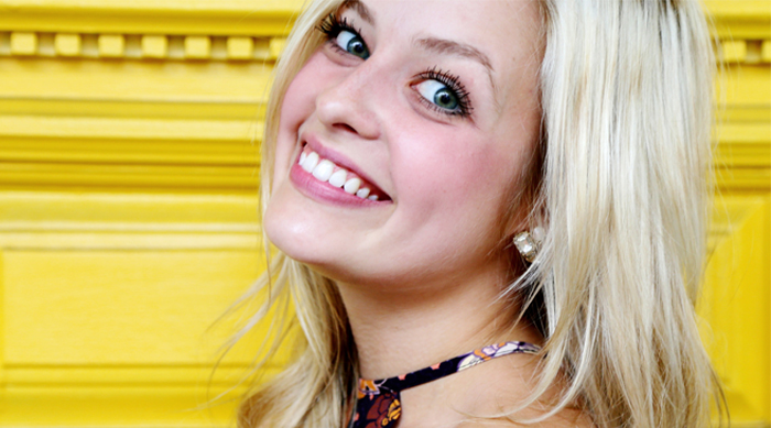 Savannah Keyes smiling against a yellow wall