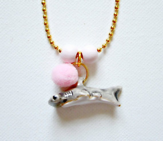 Shark necklace with a pink pom pom on it