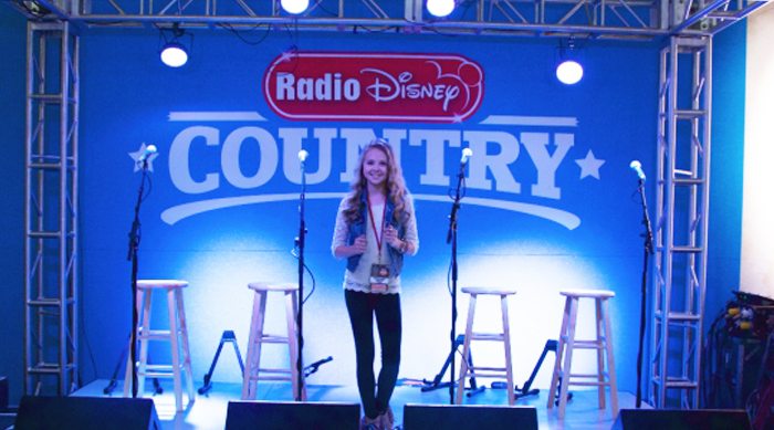 Tegan Marie standing on the Radio Disney Country stage