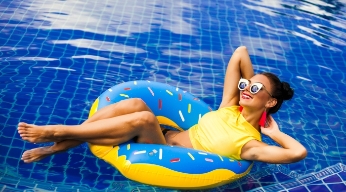 Girl in a blue donut pool inflatable wearing a yellow swimsuit in the pool