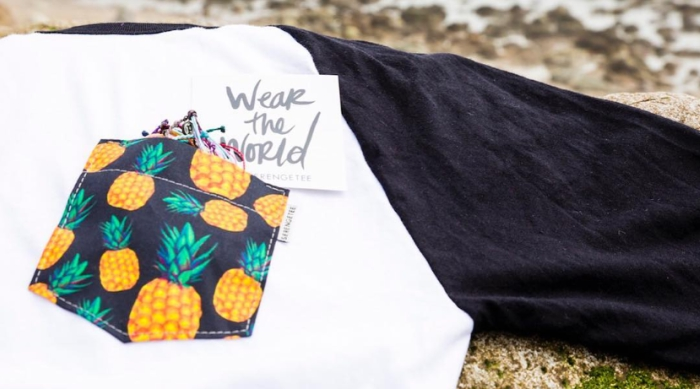 Baseball tee with a pineapple fabric pocket laid out on the beach