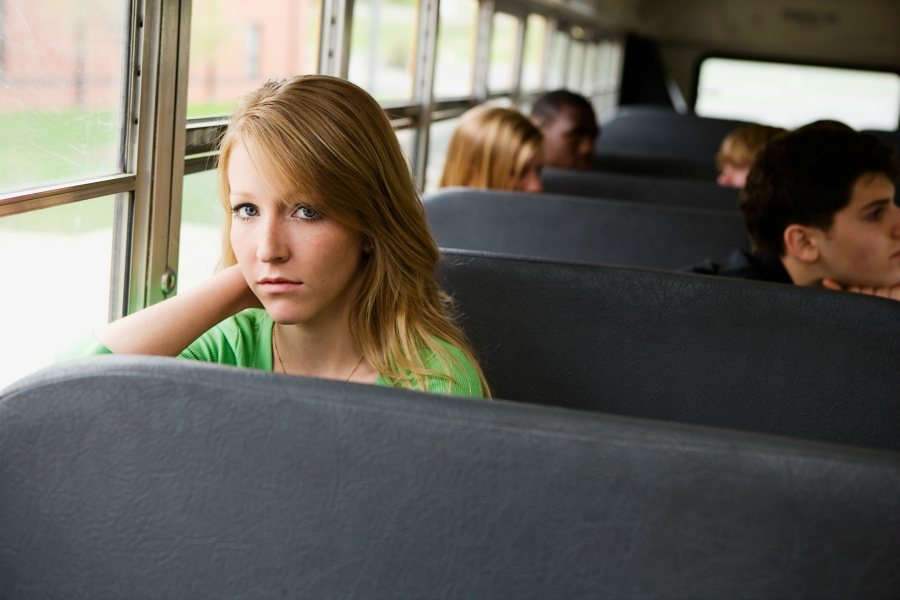 A young girl sitting on a school bus