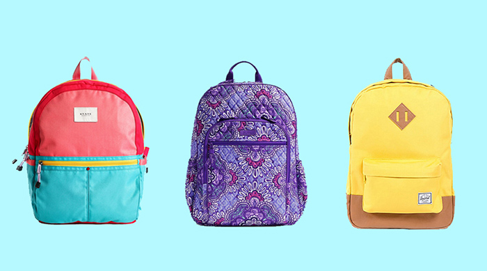 Three colorful backpacks against a pastel blue backdrop