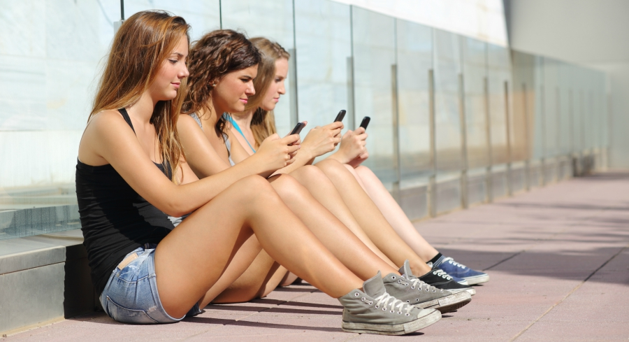 Three girls sitting next to each other while all staring at their phones