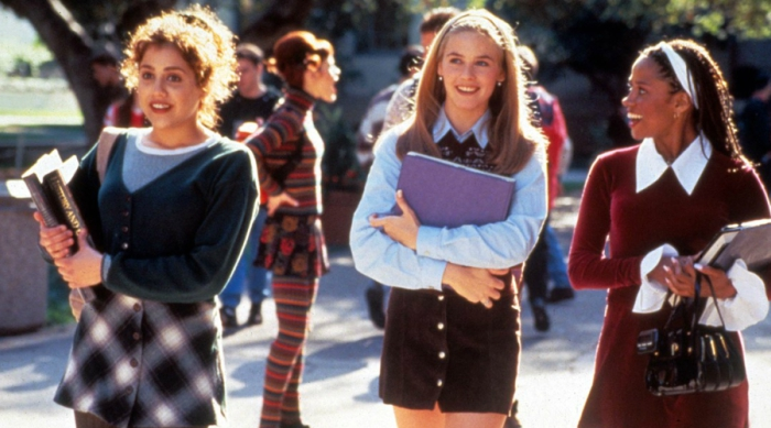 The characters of Clueless walking in a group together holding binders
