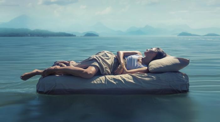 Girl sleeping on an air mattress in the lake