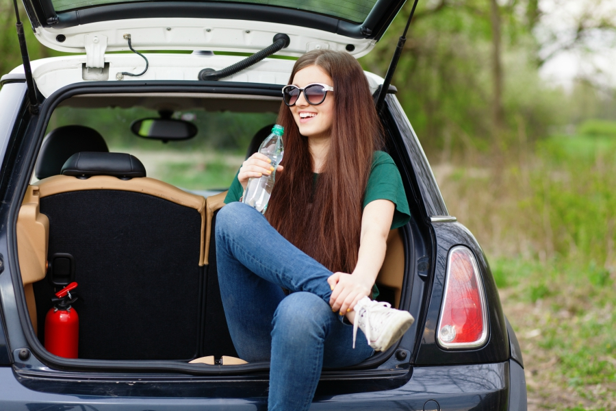 Girl drinking water and sitting in the trunk of a car
