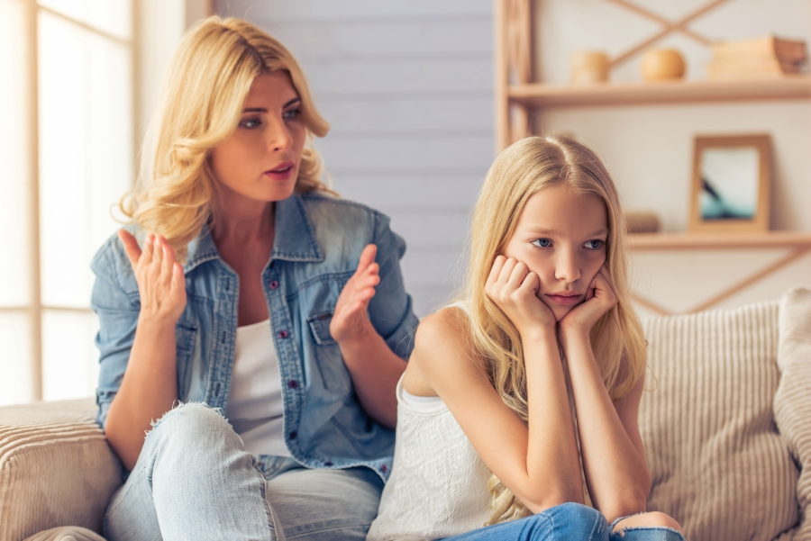 Blonde girl sitting on a couch with her head resting on her fists in an upset manner as her mom is yelling at her in the background
