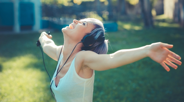 Girl listening to music with headphones on and arms stretched out wide