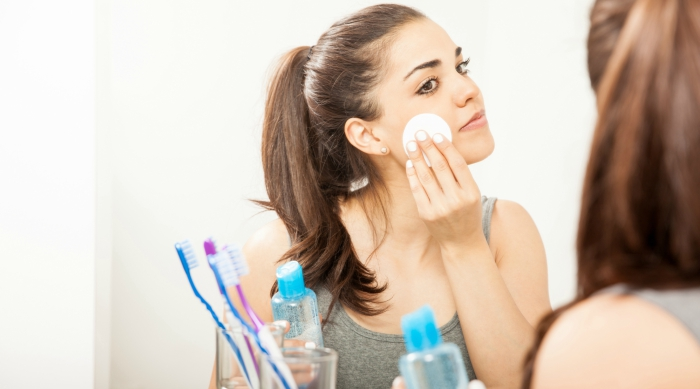 Girl removing her makeup with a makeup removing pad