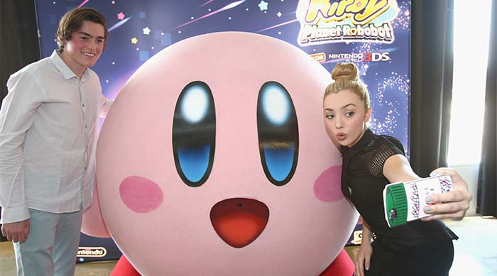 Peyton and Spencer List take a selfie in front of giant Kirby at Kirby: Planet Robobot event
