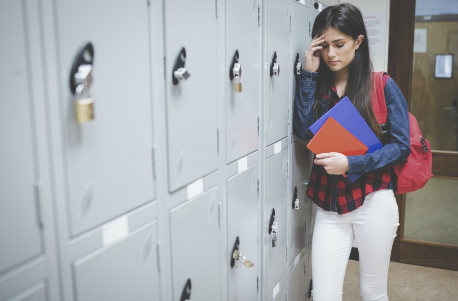 A girl stressed in front of her school locker