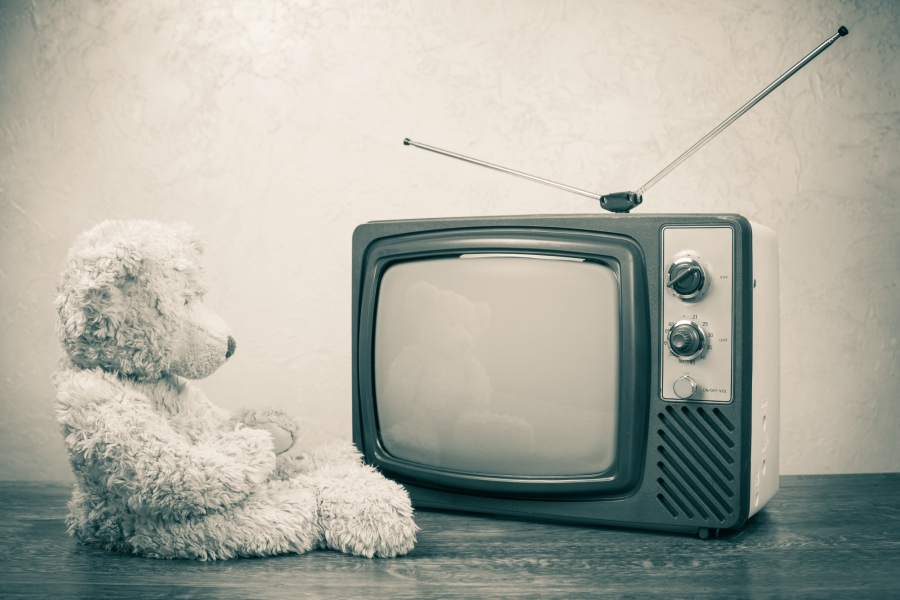 A black and white photo of a television and a teddy bear