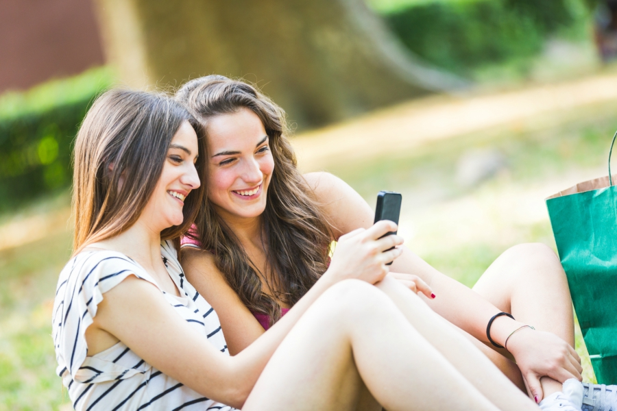 Two girls holding a phone and smiling at the screen