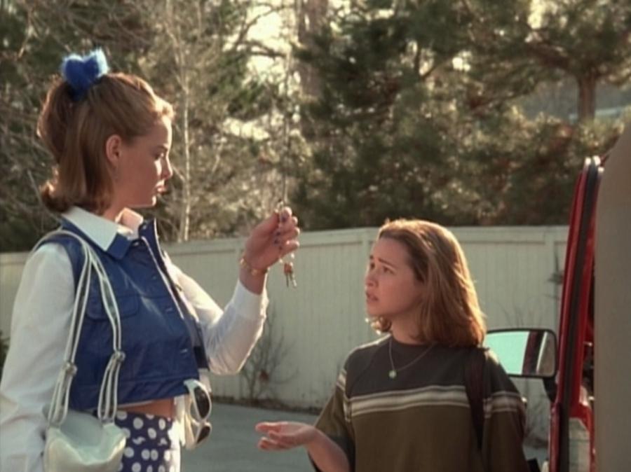 Tall girl giving car keys to short girl