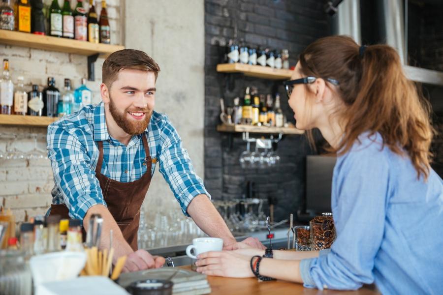 Barista talking to customer inside coffee shop.