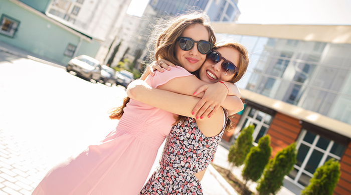 Two girls wearing sunglasses and hugging