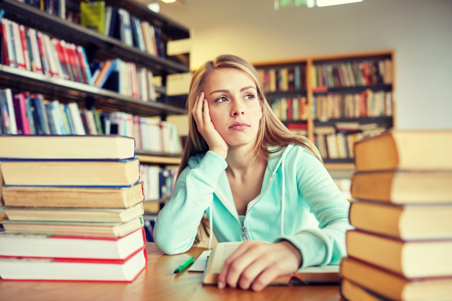 Bored girl sitting among a stack of books