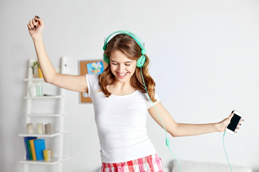 Girl with headphones on rocking out to music in her beadroom
