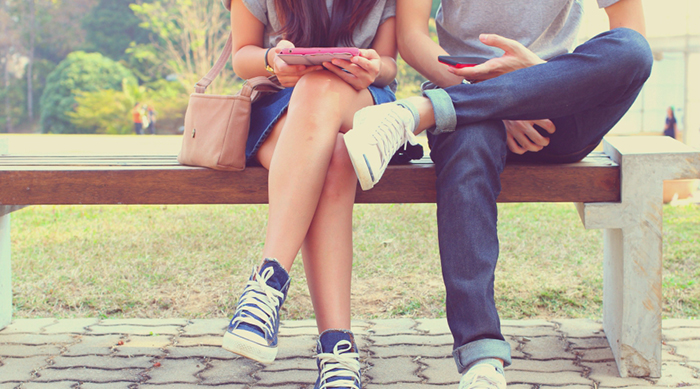 A couple sitting on a park bench with their smart phones