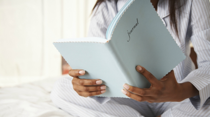 Girl wearing pajamas sitting in bed while holding a blue book that has 'journal' written on the cover