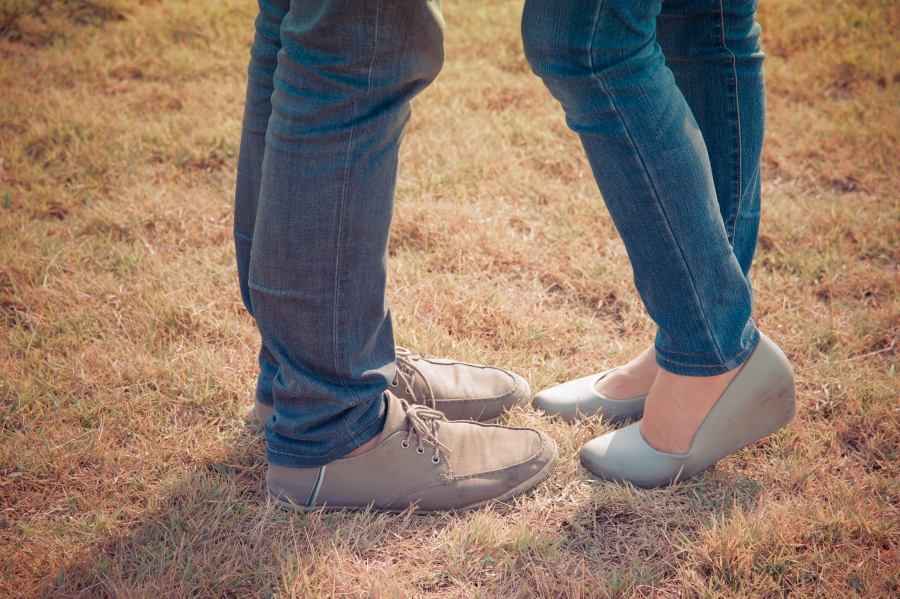 Girl and guy's feet facing each other in a grass lawn