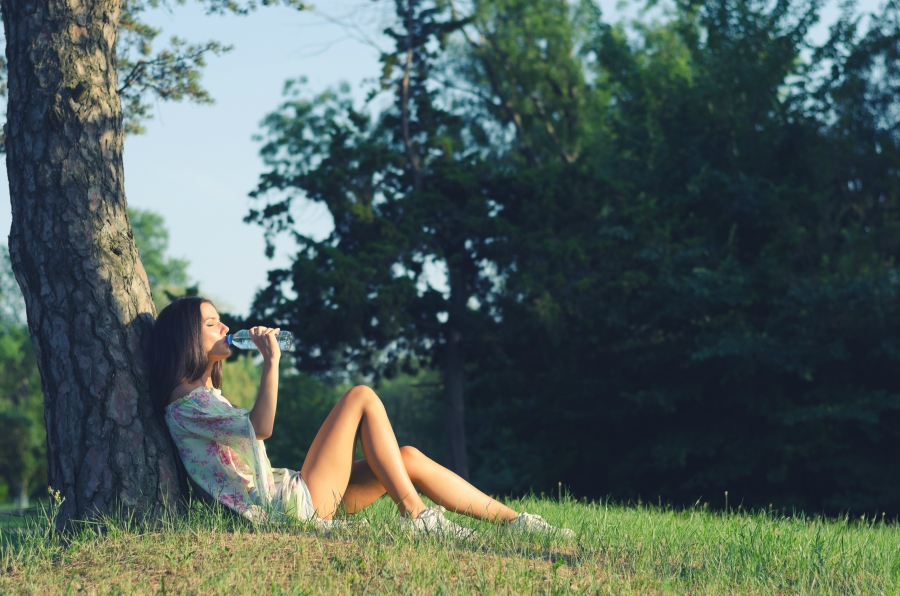Teen girl sitting under a tree and drinking water