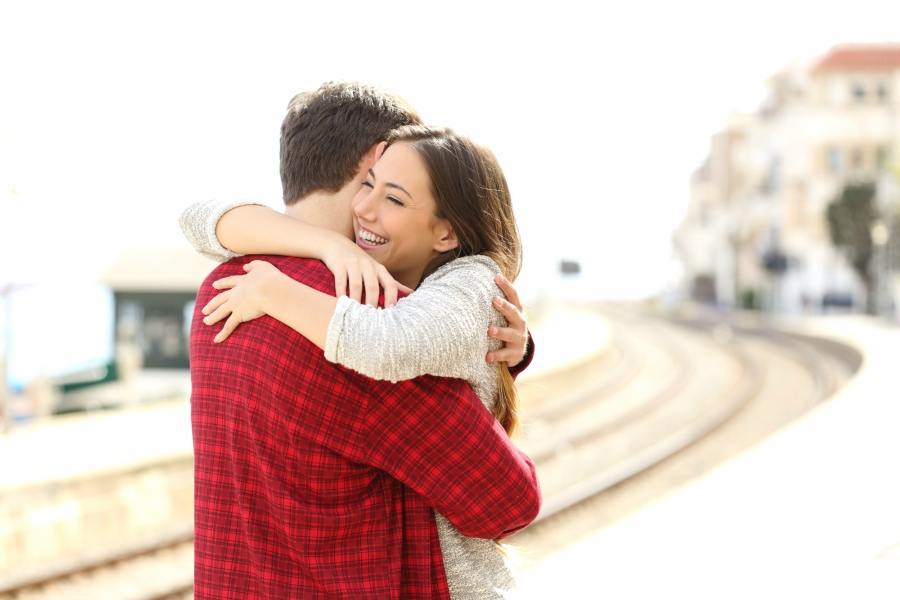 A teen girl and guy hugging by a train track
