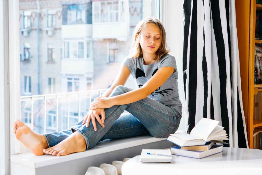 Girl looking at a book and sitting in a window sill