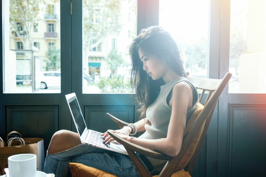 Girl checking her facebook while sitting in a coffee shop